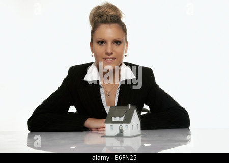 Businesswoman presenting a model house - Stock Photo