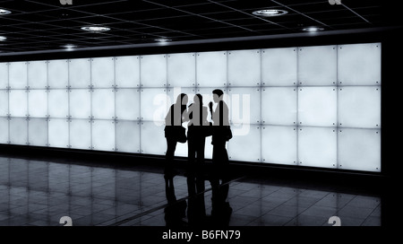 Three young people standing in front of an illuminated wall in a hall, Frankfurt, Hesse, Germany, Europe - Stock Photo