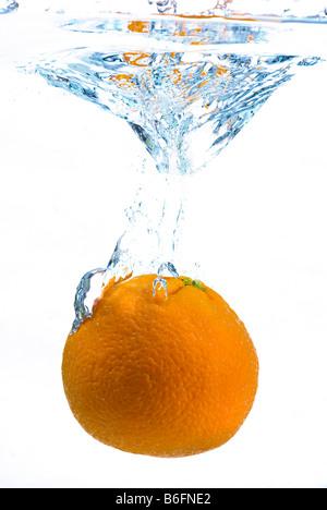 Orange falling into water - Stock Photo