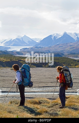 Two young women, backpackers, hikers enjoying the view at Donjek Glacier, Big Horn Creek, St. Elias Mountains, Donjek - Stock Photo