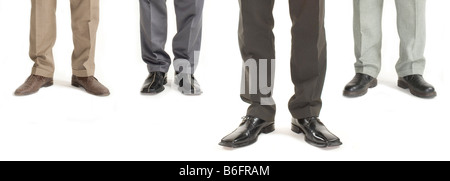 Four businessmen standing in a row with one standing further forward, detail of legs - Stock Photo