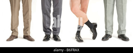 Four businessmen standing in a row, one without pants, detail of legs - Stock Photo
