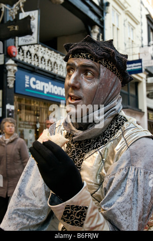 UK Cheshire Chester city centre at Christmas the silver man mime artist taking a lunch break - Stock Photo