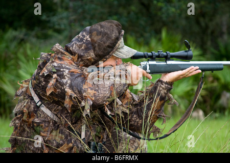 Hunter kneeling in the woods with a high powered rifle taking aim through the rifle scope - Stock Photo