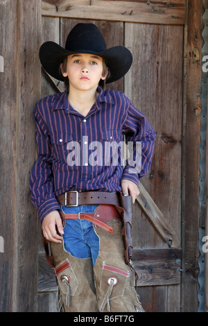 A young cowboy standing in front of an old west town - Stock Photo