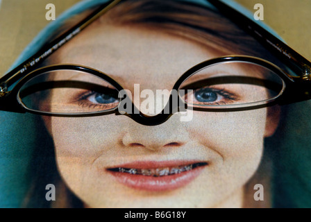 Reading glasse sitting on a picture in a newspaper, Bawdsey, Suffolk, UK. - Stock Photo