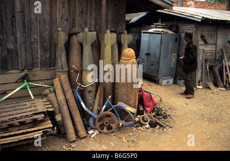 Scrap metal dealer and yard with US Vietnam war-era war scrap, cluster bomb casings, missiles and mortars, Phonsavan, - Stock Photo