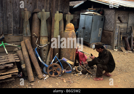 A scrap metal dealer and junk yard with US Vietnam war-era war scrap, cluster bomb casings and missiles, Phonsavan, - Stock Photo