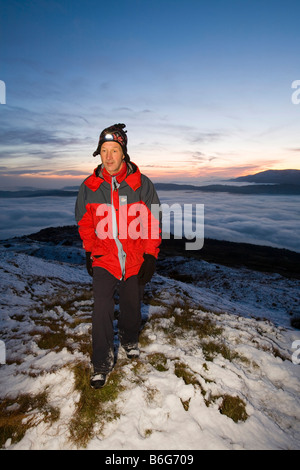 A walker on Wansfell Pike in the Lake District UK with valley mist below - Stock Photo
