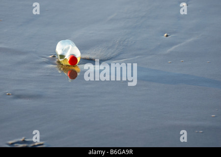 One plastic bottle detail abandoned lying in shallow sea water alone - Stock Photo