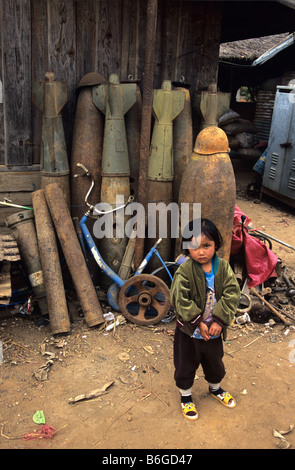 A Laotian girl in front of war scrap from US Vietnam War-era including cluster bomb casings and missiles, Phonsavan, - Stock Photo