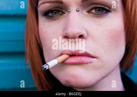 Young red haired pale skinned Irish girl woman with a cigarette in her mouth looking sultry moody staring ahead - Stock Photo