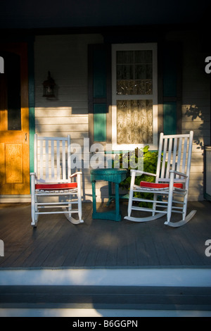 Evening sun on a quaint Victorian porch with two rocking chairs and a window with lace curtains. - Stock Photo