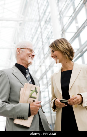 Older man talking to younger woman - Stock Photo
