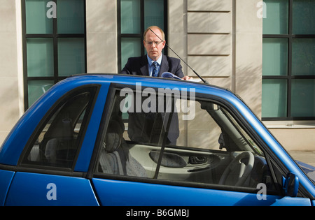 Man looking at papers on top of car - Stock Photo