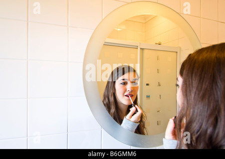 Horizontal close up portrait of an attractive young teenage girl putting on lip gloss in a bathroom mirror - Stock Photo