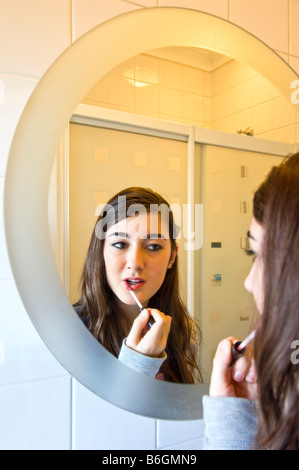 Vertical close up portrait of an attractive young teenage girl putting on lip gloss in a bathroom mirror - Stock Photo