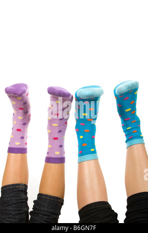 Vertical close up portrait of two pairs of feet in spotty socks in the air against a white background - Stock Photo