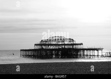 A black and white image of the burnt out remains Brightons West pier on a calm day, taken from Brighton beach - Stock Photo