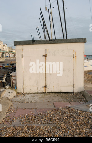 A storage beach hut closed up for winter in Hove on the pathway into Brighton. Boat masts can be seen behind the - Stock Photo