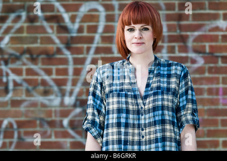 Red haired young irish pale skinned woman with a piercing in the bridge of her nose graffiti covered brick wall - Stock Photo