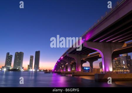 Magenta lights of public art work highlights McArthur Causeway bridge over Biscayne Bay Miami Florida - Stock Photo