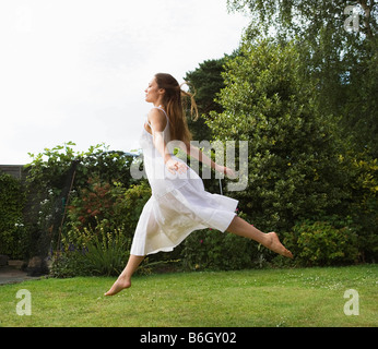 Woman jumping in air in garden - Stock Photo
