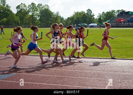 Competitors run at a High School District Track Meet - Stock Photo