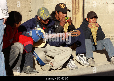 Teenagers playing musical instruments on the street of San Antonio de los Cobres a small town in Salta district - Stock Photo