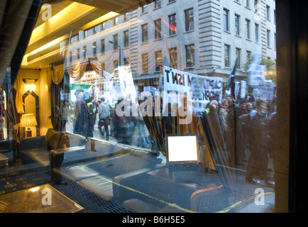 a view of the crowd during the 2008 campaign against climate change march through a furniture shop window - Stock Photo
