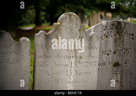 A close up of  a tightly spaced grouping of 3 old colonial/early American marble tombstones. - Stock Photo