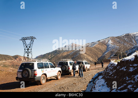 Tourists and 4x4 offroad vehicles on dirt road through High Atlas Mountains in winter. Morocco - Stock Photo