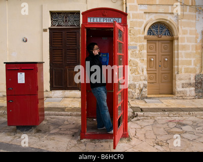 A man talks on the phone in a British red phone booth. - Stock Photo