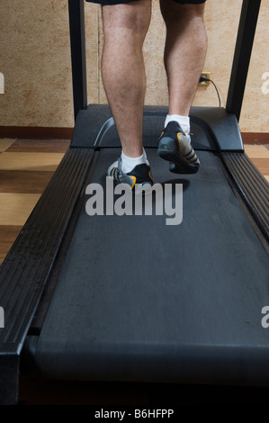 Rear view of a man exercising on treadmill - Stock Photo