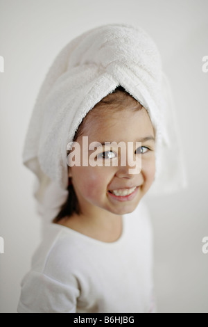 Five year old girl with wet hair wrapped in towel - Stock Photo