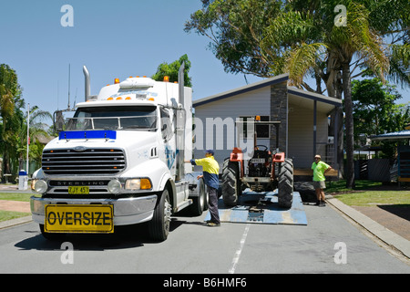 a prefabricated or mobile home attached to a tractor ready to be placed on the site - Stock Photo