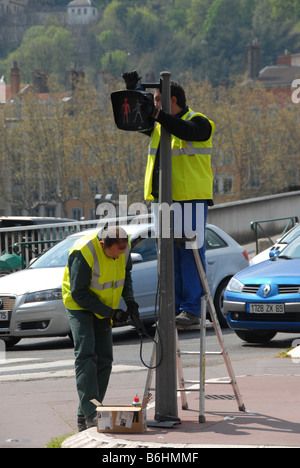 Two council workers repairing a faulty pedestrian crossing traffic light at a busy road junction in Lyon France - Stock Photo