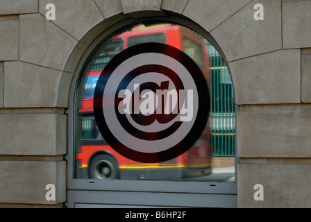 @ sign (at sign) on mirrored glass window with red doubledecker bus in blurred motion behind, Clerkenwell, London, - Stock Photo