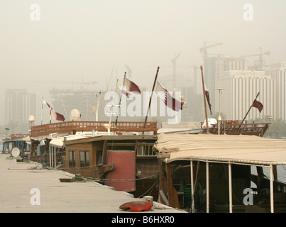 Qatari flags decorating traditional boats at Doha Bay and hazy skyscraper skyline, Qatar, Middle East - Stock Photo