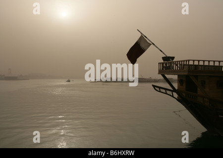 Qatari flag on traditional boat in sunlit haze, Doha Bay,Doha, Qatar, Middle East - Stock Photo
