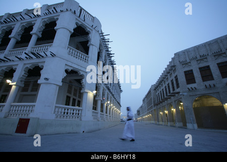 Man walking past traditional whitewash buildings at Souq Waqif market with protruding 'shandal' beams at dusk, Doha, - Stock Photo