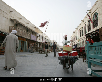 Street scene with market trader and goods wheelbarrow at the Souq Waqif market, Doha, Qatar, Middle East - Stock Photo