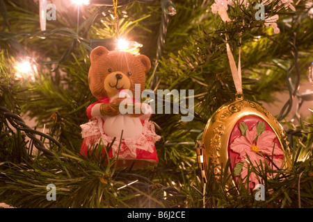 Christmas teddy bear with cake and gold ornaments hanging on a tree indoors - Stock Photo