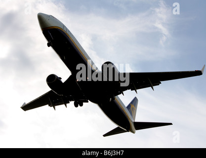 A close up of a ryanair passenger airplane flying overhead and coming in to land - Stock Photo