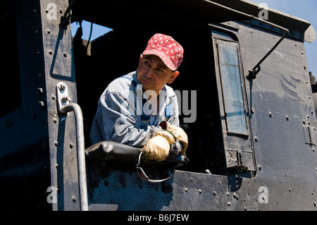 Train engineer looking out of cab on Old fashioned vintage locomotive train engine - Stock Photo