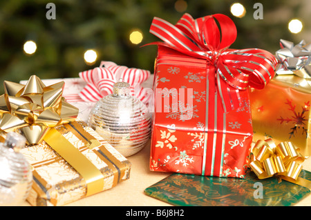 Scene of wrapped Christmas Gifts on festive table with lighted tree in background. - Stock Photo