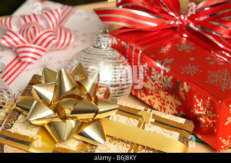 Wrapped Christmas presents with ornaments and baubles on table - Stock Photo