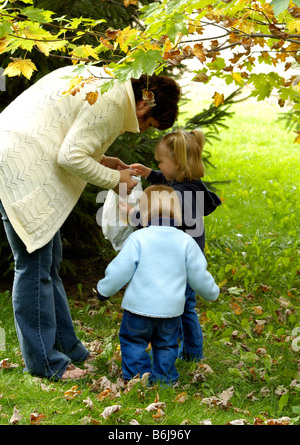 Two young girls run to discover what Nana has in the bag - Stock Photo
