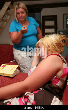 Moody teenage girl being told off by her mother - Stock Photo