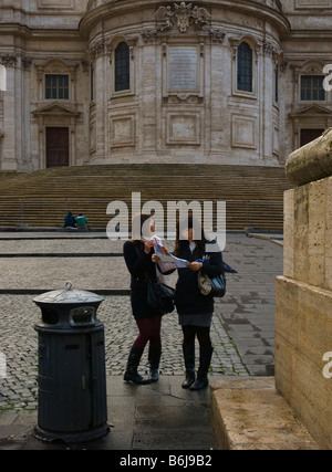 Two female tourists looking at a map in front of Basilica di Santa Maria Maggiore at Piazza dell Aquilino in Rome - Stock Photo